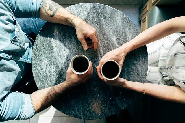 カップを近づけて珈琲を飲むカップル