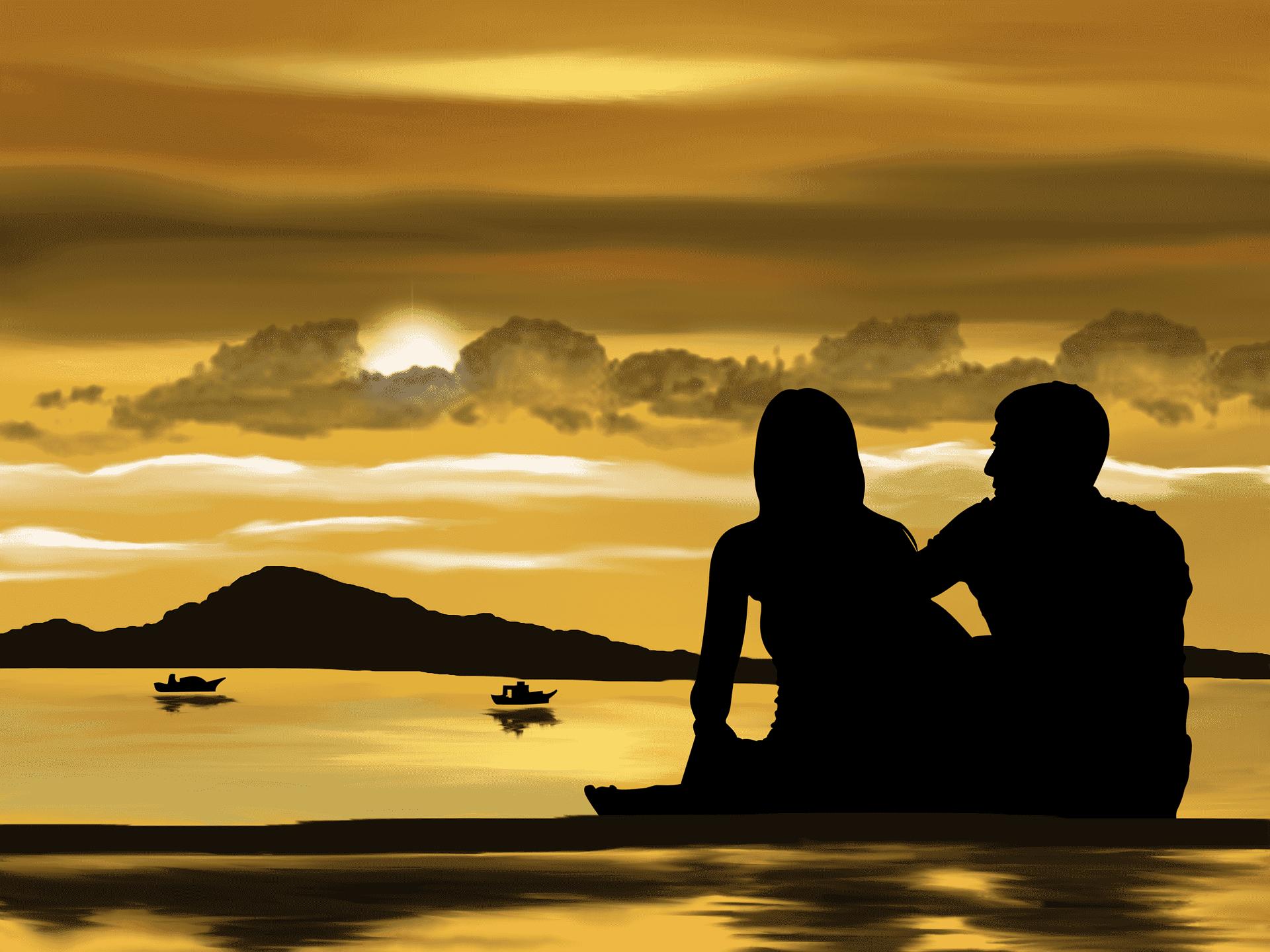 海辺で夕日を見るカップル