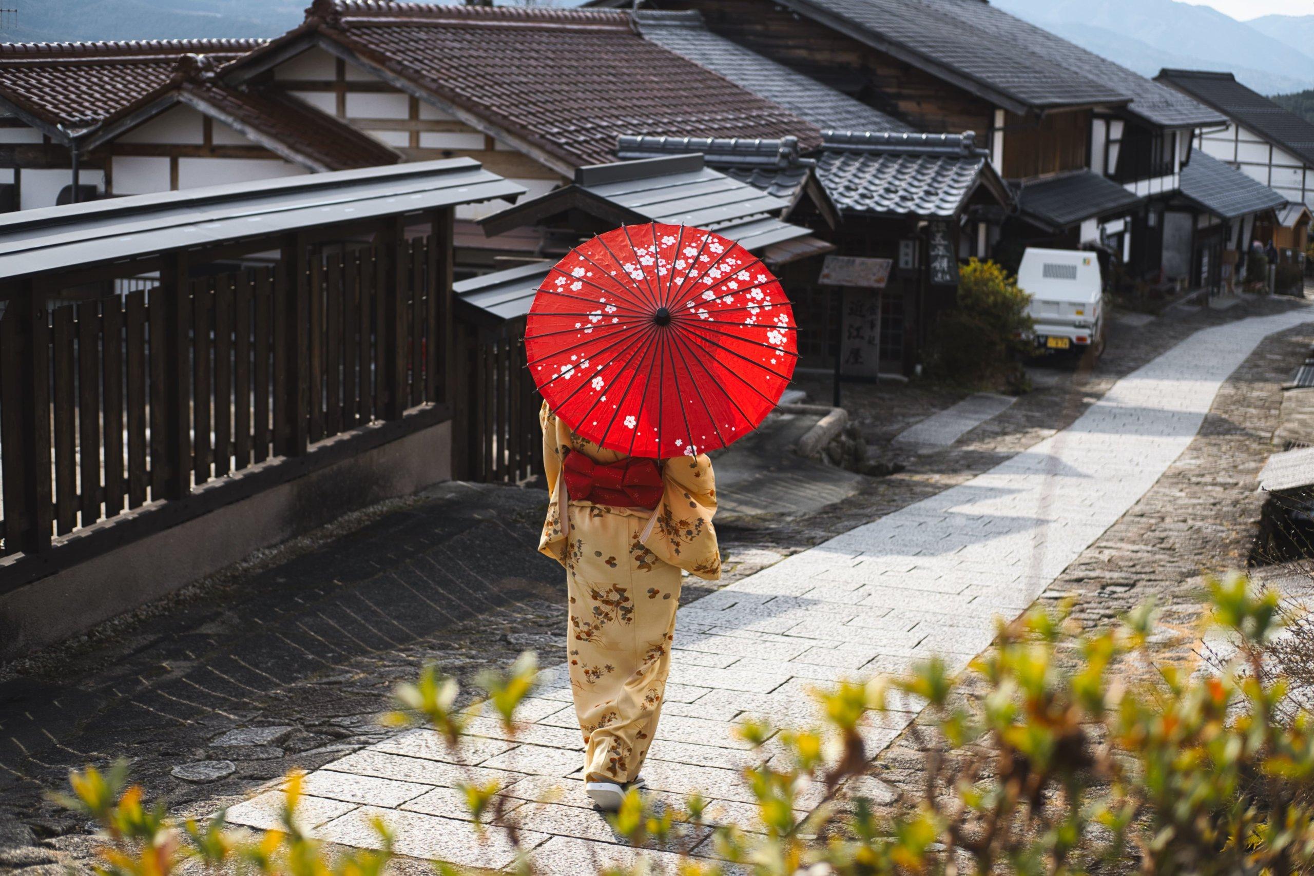 和柄の日傘を挿して歩く女性